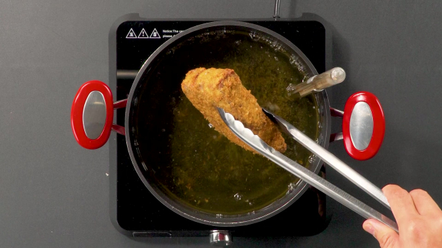 Deep frying steak in a pot of oil with tongs