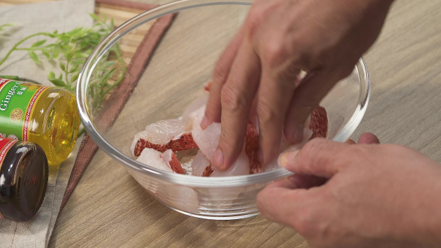 Mixing marinade into fish slices with fingers