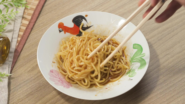 Mixing yellow noodles and sauce with chopsticks in rooster bowl