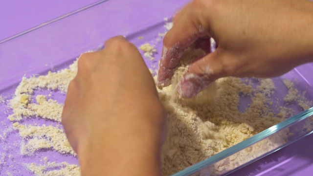 Pinching butter into flour with fingers to form crumbles