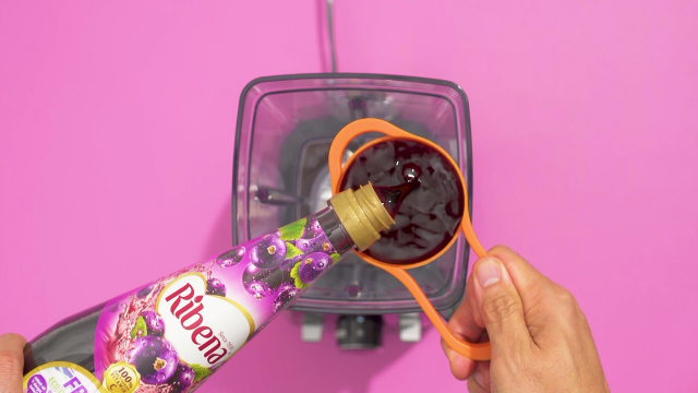 Measuring ribena cordial with a cup to pour into blender